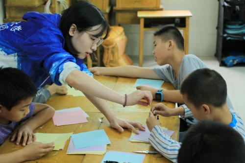 x支教團成員在教孩子做手工.png