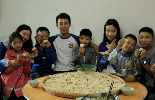 x支教團成員和孩子們在展示包好的餃子.png